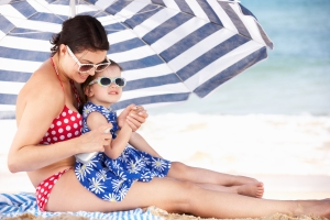 Mother And Daughter Under Beach Umbrella Putting On Sun Cream