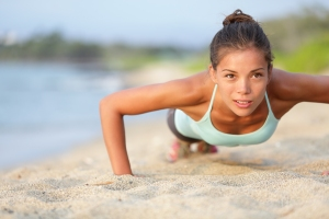 Push-ups fitness woman doing pushups outside on beach. Fit femal