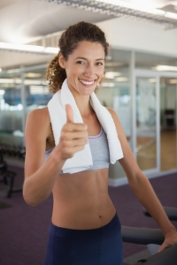 Fit woman wearing towel around shoulders showing thumbs up at th