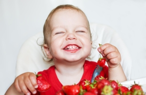 Happy Toddler Boy Eating Strawberries