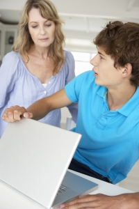 Mother supervising teenage son using laptop