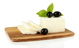 Sheep milk cheese with basil and black olives, on cutting board