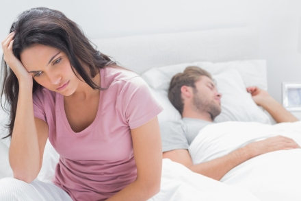 Anxious woman thinking in her bed next to her sleeping partner