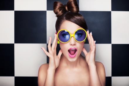 Attractive surprised young woman wearing sunglasses on checkered