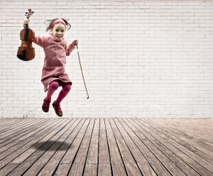 little girl with violin jumping on a room with white bricks wall