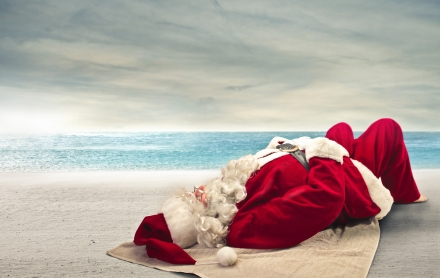 Santa Claus sunbathing lying on the beach