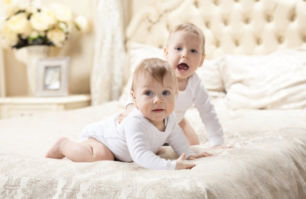 Two baby boys playing on bed