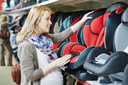 woman choosing child car seat for newborn baby in shop supermark