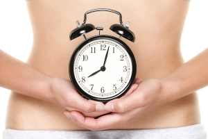 Biological clock ticking - woman holding clock in front of stoma