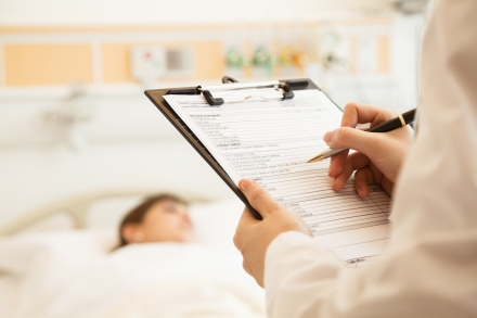Close up of doctor writing on a medical chart with patient lying
