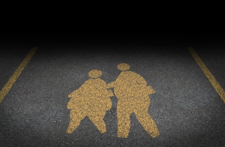 Obesity in children and childhood obese concept with a yellow painted asphalt road sign showing an icon of overweight kids and young students as a warning to the hazards of eating junk food and fatty fast food.